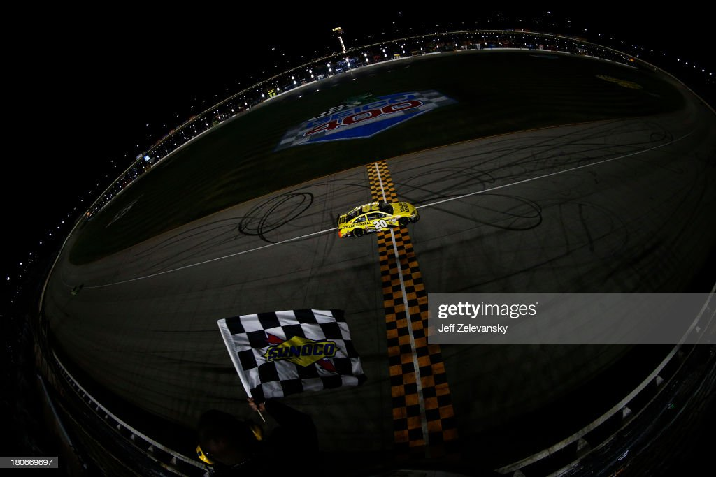 Matt Kenseth, driver of the #20 Dollar General Toyota, races past the checkered flag to win the NASCAR Sprint Cup Series Geico 400 at Chicagoland Speedway on September 15, 2013 in Joliet, Illinois.