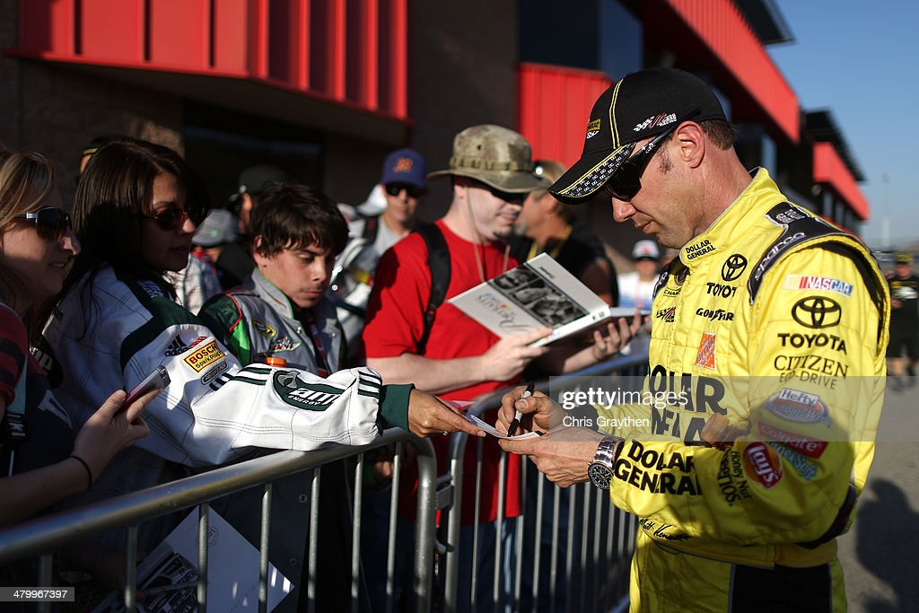 Matt Kenseth, driver of the #20 Dollar General Toyota, signs autographs for fans during qualifying for the NASCAR Sprint Cup Series Auto Club 400 at Auto Club Speedway on March 21, 2014 in Fontana, California.
