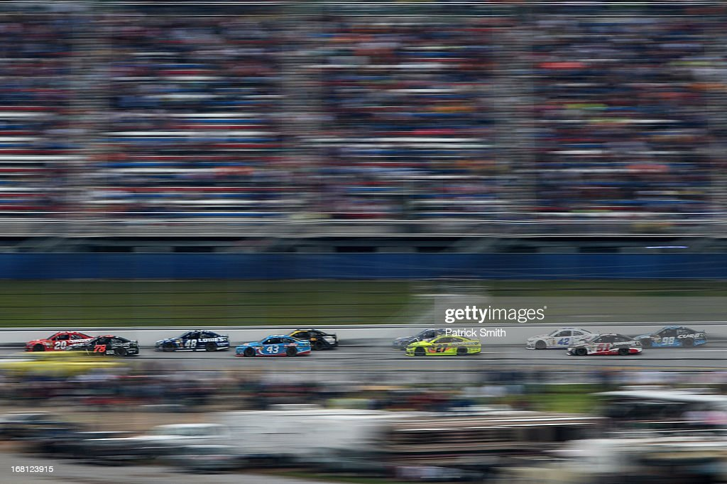 Matt Kenseth, driver of the #20 Home Depot / Husky Toyota, and Kurt Busch, driver of the #78 Furniture Row / Beautyrest Chevrolet, lead a pack of cars down the backstretch during the NASCAR Sprint Cup Series Aaron's 499 at Talladega Superspeedway on May 5, 2013 in Talladega, Alabama.