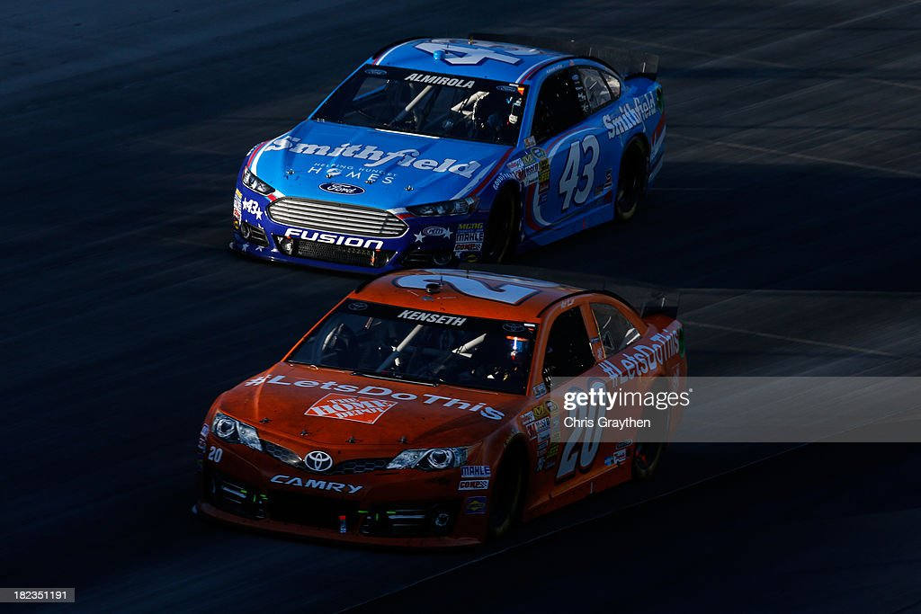 Matt Kenseth, driver of the #20 Home Depot 'Let's Do This' Toyota, leads Aric Almirola, driver of the #43 Smithfield Ford, during the NASCAR Sprint Cup Series AAA 400 at Dover International Speedway on September 29, 2013 in Dover, Delaware.
