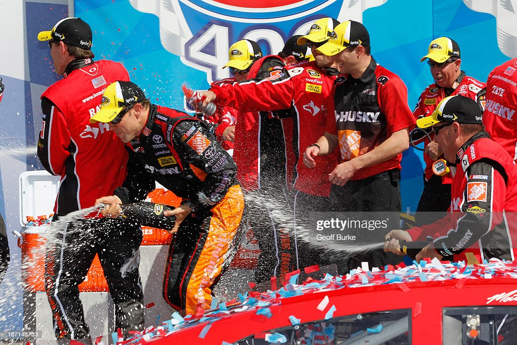 Matt Kenseth (l), driver of the #20 The Home Depot/Husky Toyota, celebrates in victory lane after winning the NASCAR Sprint Cup Series STP 400 at Kansas Speedway on April 21, 2013 in Kansas City, Kansas.