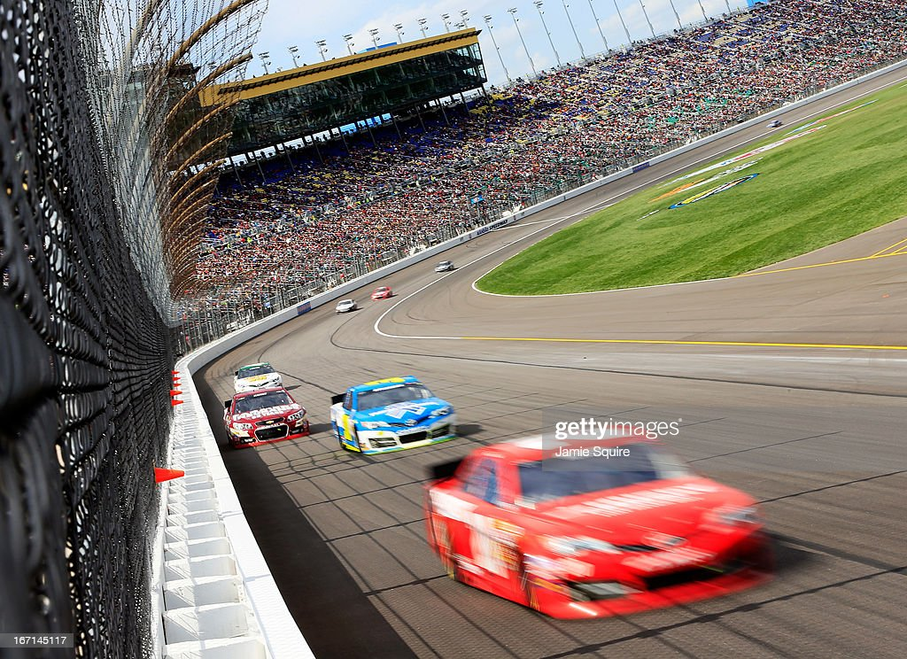 Matt Kenseth, driver of the #20 The Home Depot/Husky Toyota, leads a group of cars during the NASCAR Sprint Cup Series STP 400 at Kansas Speedway on April 21, 2013 in Kansas City, Kansas.