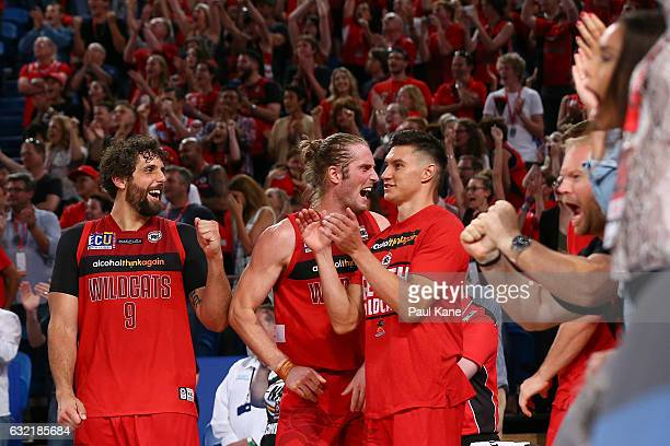 Matt Knight Jesse Wagstaff and Jarred Kenny of the Wildcats celebrate successful free throws made by Bryce Cotton to tie the game up during the round...