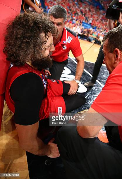 Matt Knight of the Wildcats is attended to by team medical staff after taking a charge from Cam Bairstow of the Bullets during the round nine NBL...