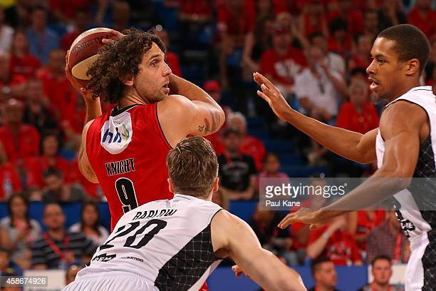 Matt Knight of the Wildcats looks to pass the ball against David Barlow and Stephen Dennis of United during the round five NBL match between the...
