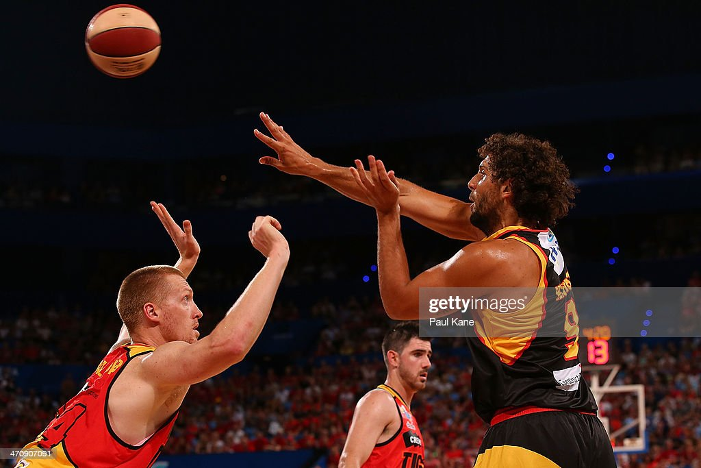 Matt Knight of the Wildcats passes the ball against Adam Ballinger of the Tigers during the round 19 NBL match between the Perth Wildcats and the Melbourne Tigers at Perth Arena on February 21, 2014 in Perth, Australia.