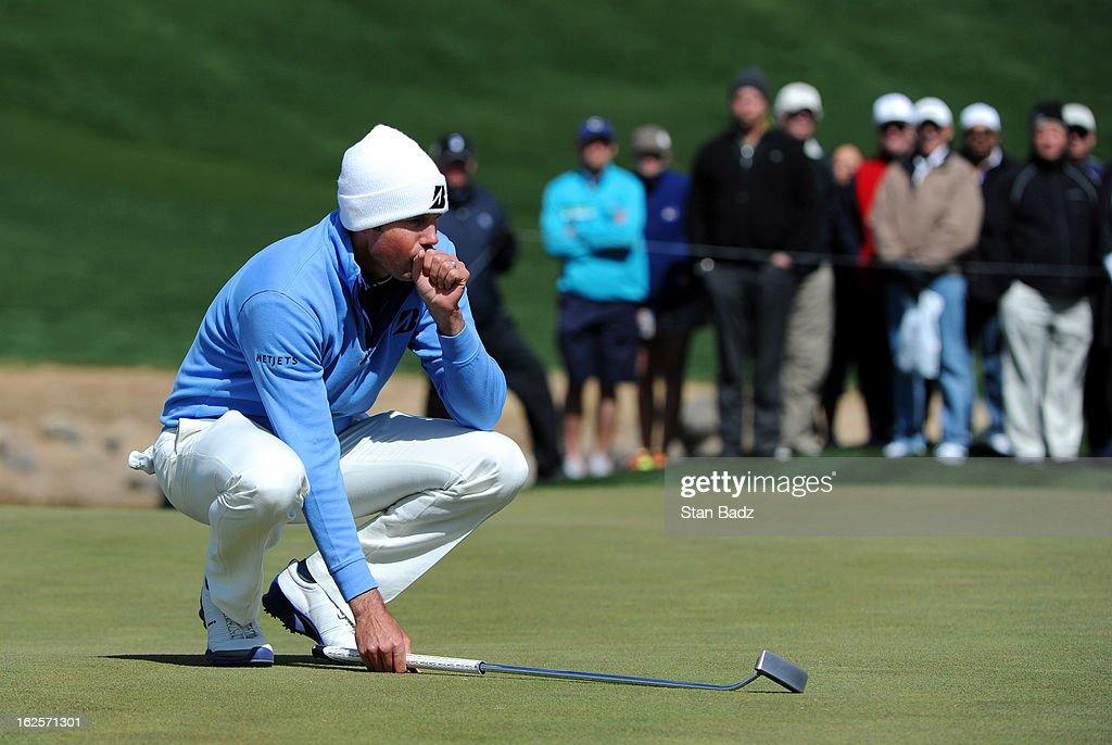 Matt Kuchar keeps his hands warm as he lines his putt on the second hole during the final round of the World Golf Championships-Accenture Match Play Championship at The Golf Club at Dove Mountain on February 24, 2013 in Marana, Arizona.