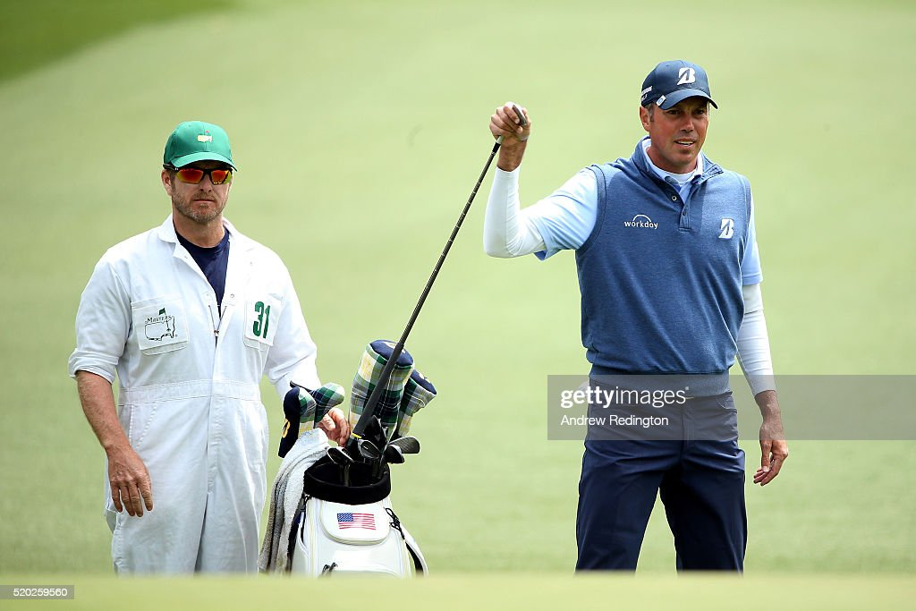 Matt Kuchar of the United States pulls a club from his bag as caddie John Wood looks on during the final round of the 2016 Masters Tournament at Augusta National Golf Club on April 10, 2016 in Augusta, Georgia.