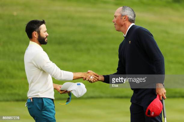 Matt Kuchar of the US Team shakes hands with Adam Hadwin of Canada and the International Team on the 15th green during Saturday foursome matches of...