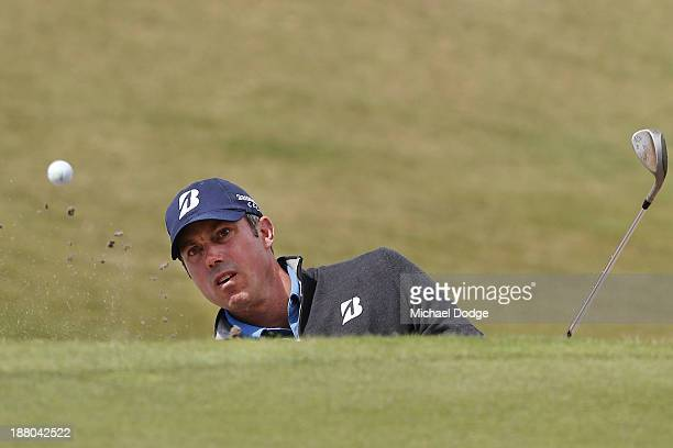 Matt Kuchar of the USA chips the ball out of the bunker during round two of the 2013 Australian Masters at Royal Melbourne Golf Course on November 15...