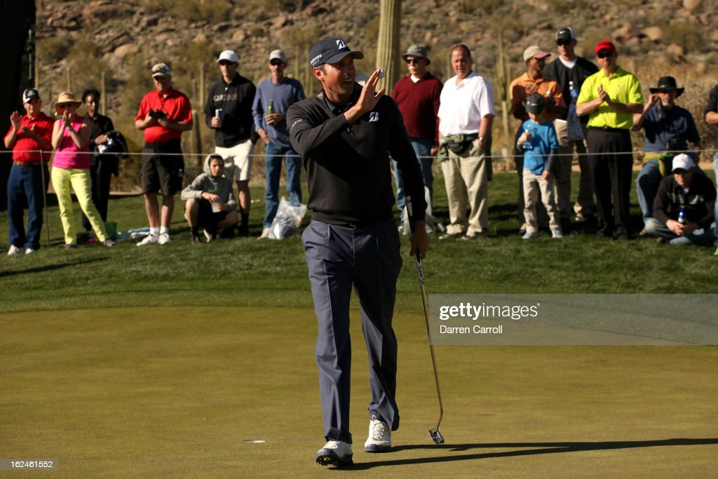 Matt Kuchar waves his ball to the gallery as he celebrates after he made a birdie putt to win the hole on the 15th hole green during the quarterfinal round of the World Golf Championships - Accenture Match Play at the Golf Club at Dove Mountain on February 23, 2013 in Marana, Arizona.