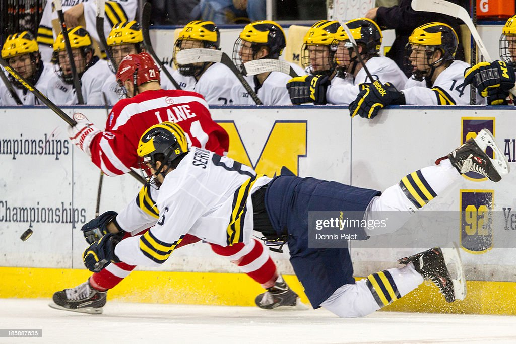 Matt Lane #21 of the Boston University Terriers battles for the puck against Brennan Serville #6 of the Michigan Wolverines on October 25, 2013 at Yost Ice Arena in Ann Arbor, Michigan.