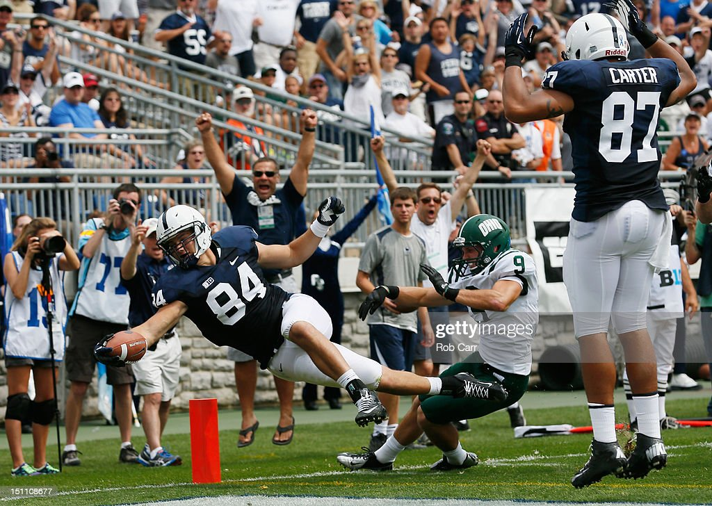 Matt Lehman #84 of the Penn State Nittany Lions lepas into the end zone in for a touchdown in front of Josh Kristoff #9 of the Ohio Bobcats after catching a pass during the second quarter at Beaver Stadium on September 1, 2012 in State College, Pennsylvania. Looking on at right is Kyle Carter #87.