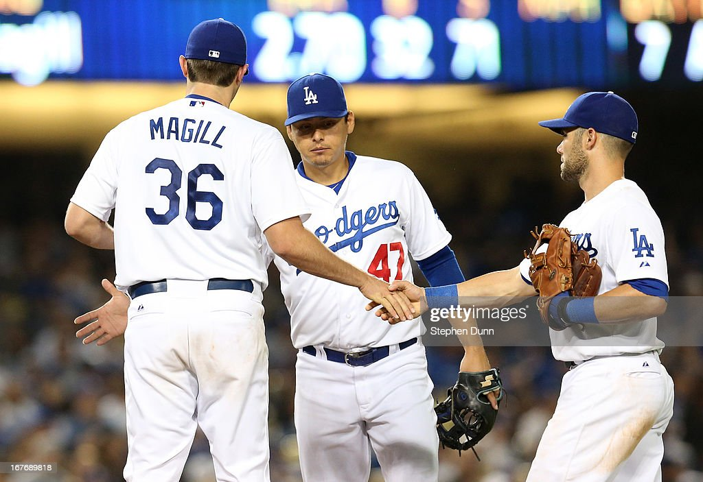 Matt Magill #36 of the Los Angeles Dodgers is congratulated by Luis Cruz #47 and <a gi-track='captionPersonalityLinkClicked' href=/galleries/search?phrase=Skip+Schumaker&family=editorial&specificpeople=640599 ng-click='$event.stopPropagation()'>Skip Schumaker</a> #3 as Magill is relieved in the seventh inning after his first Major League start and appearance, against the Milwaukee Brewers at Dodger Stadium on April 27, 2013 in Los Angeles, California.