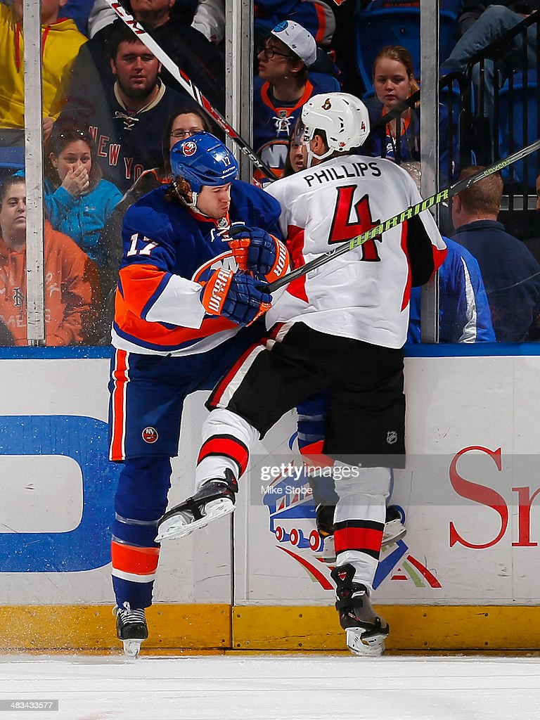 Matt Martin #17 of the New York Islanders and Chris Phillips #4 of the Ottawa Senators come together at the boards at Nassau Veterans Memorial Coliseum on April 8, 2014 in Uniondale, New York.