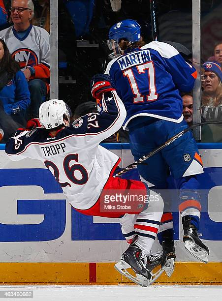 Matt Martin of the New York Islanders and Corey Tropp of the Columbus Blue Jackets collide along the boards at Nassau Veterans Memorial Coliseum on...