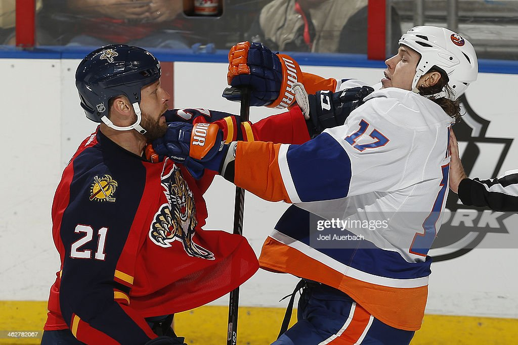 Matt Martin of the New York Islanders and Krys Barch of the Florida Panthers come together during third period action at the BBT Center on January 14...