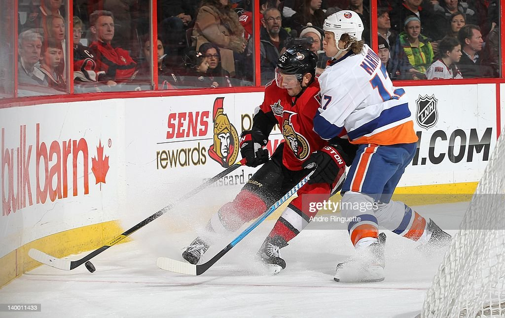 Matt Martin #17 of the New York Islanders challenges <a gi-track='captionPersonalityLinkClicked' href=/galleries/search?phrase=Sergei+Gonchar&family=editorial&specificpeople=202470 ng-click='$event.stopPropagation()'>Sergei Gonchar</a> #55 of the Ottawa Senators for the puck along the boards at Scotiabank Place on February 26, 2012 in Ottawa, Ontario, Canada.