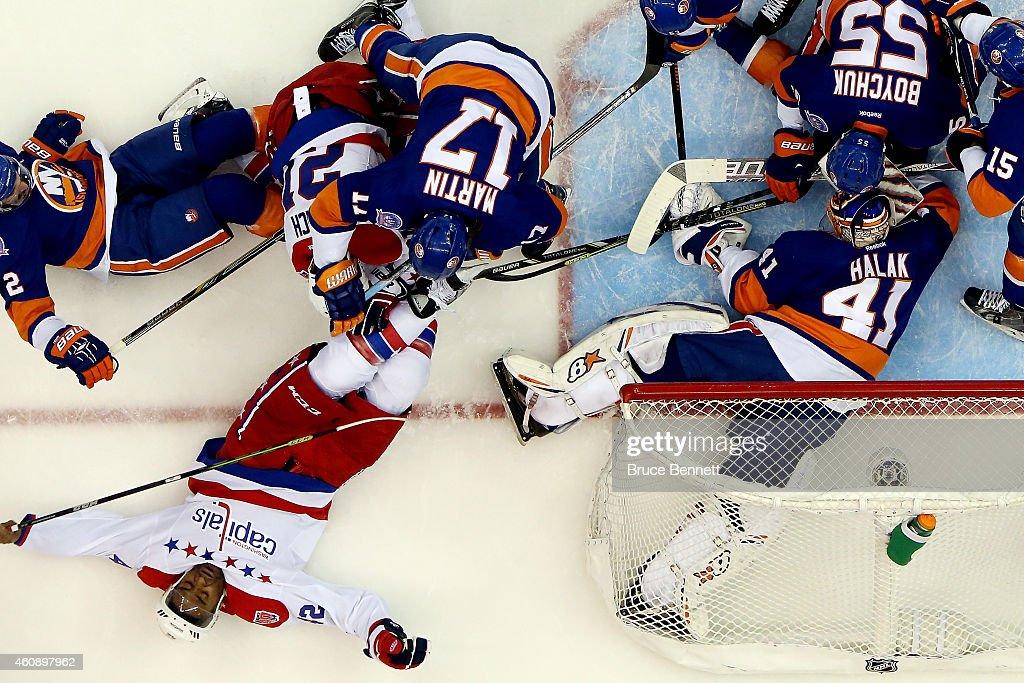 Matt Martin of the New York Islanders checks Joel Ward of the Washington Capitals during a game at the Nassau Veterans Memorial Coliseum on December...