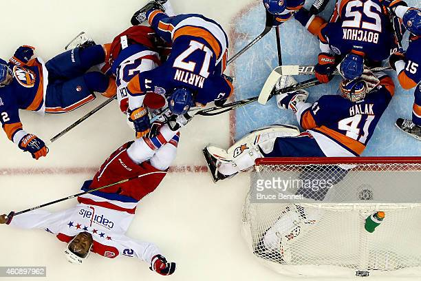 Matt Martin of the New York Islanders checks Joel Ward of the Washington Capitals during a game at the Nassau Veterans Memorial Coliseum on December...