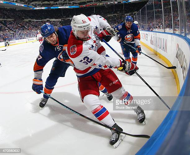 Matt Martin of the New York Islanders checks Mike Green of the Washington Capitals into the boards during the second period in Game Four of the...