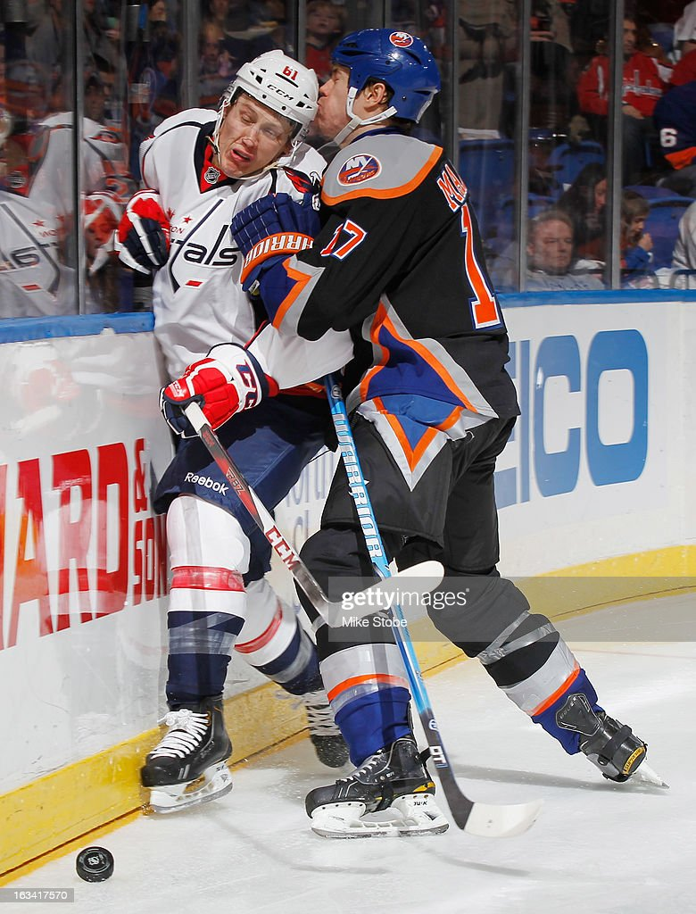 Matt Martin #17 of the New York Islanders checks Steven Oleksy #61 of the Washington Capitals into the boards at Nassau Veterans Memorial Coliseum on March 9, 2013 in Uniondale, New York. The Islanders defeated the Capitals 5-2.