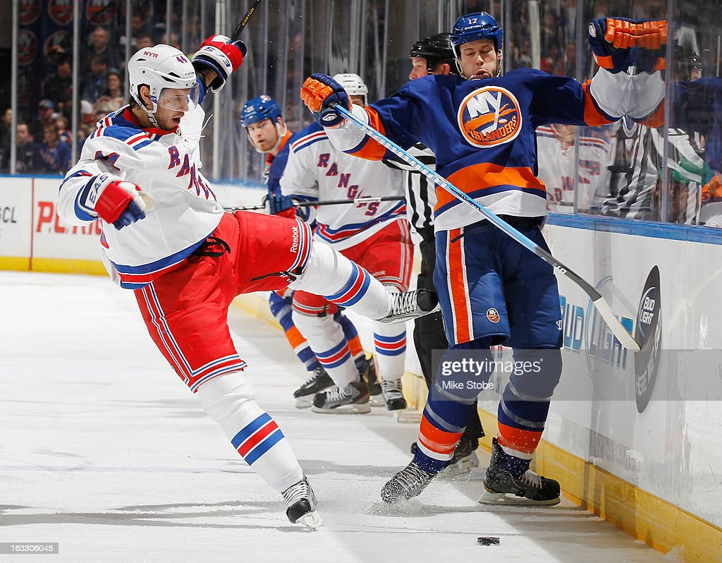 Matt Martin #17 of the New York Islanders collides with Steve Eminger #44 of the New York Rangers at Nassau Veterans Memorial Coliseum on March 7, 2013 in Uniondale, New York.