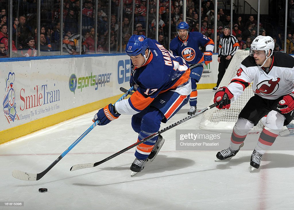 Matt Martin #17 of the New York Islanders controls the puck against Adam Henrique #14 of the New Jersey Devils during the game on February 16, 2013 at Nassau Veterans Memorial Coliseum in Uniondale, New York.