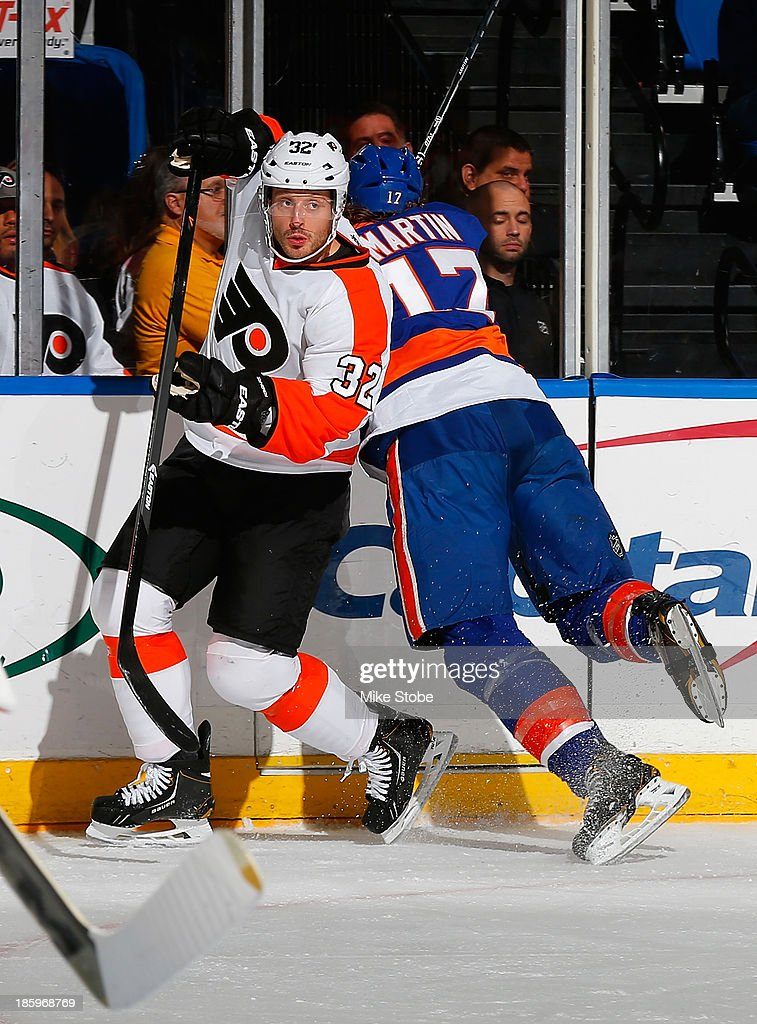 Matt Martin #17 of the New York Islanders falls into the boards as Mark Streit #32 of the Philadelphia Flyers evades his check at Nassau Veterans Memorial Coliseum on October 26, 2013 in Uniondale, New York.