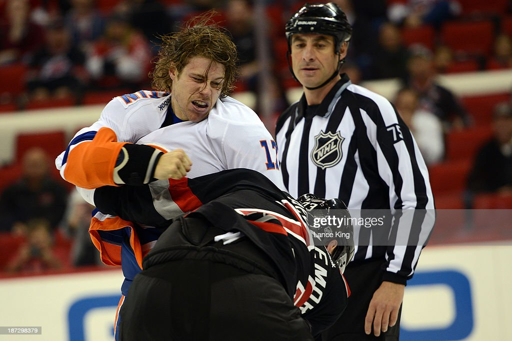 Matt Martin #17 of the New York Islanders fights with <a gi-track='captionPersonalityLinkClicked' href=/galleries/search?phrase=Brett+Bellemore&family=editorial&specificpeople=4270909 ng-click='$event.stopPropagation()'>Brett Bellemore</a> #73 of the Carolina Hurricanes at PNC Arena on November 7, 2013 in Raleigh, North Carolina.