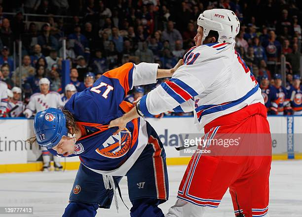 Matt Martin of the New York Islanders gets tangled up with Stu Bickel of the New York Rangers at Nassau Veterans Memorial Coliseum on February 24...
