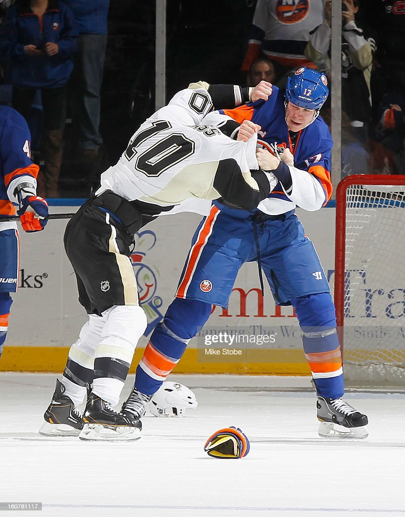 Matt Martin #17 of the New York Islanders gets tangled up with Tanner Glass #10 of the Pittsburgh Penguins at Nassau Veterans Memorial Coliseum on Febuary 5, 2013 in Uniondale, New York.