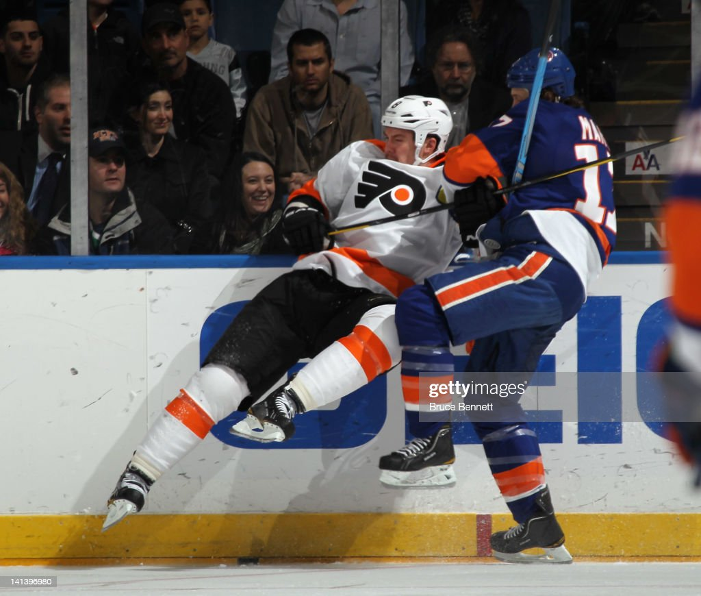 Matt Martin #17 of the New York Islanders hits <a gi-track='captionPersonalityLinkClicked' href=/galleries/search?phrase=Andreas+Lilja&family=editorial&specificpeople=210774 ng-click='$event.stopPropagation()'>Andreas Lilja</a> #6 of the Philadelphia Flyers into the boards at the Nassau Veterans Memorial Coliseum on March 15, 2012 in Uniondale, New York.