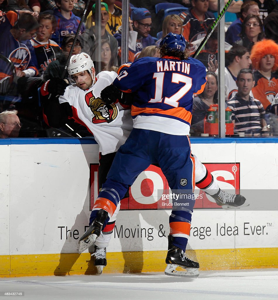 Matt Martin #17 of the New York Islanders hits Clarke MacArthur #16 of the Ottawa Senators into the boards during the second period at the Nassau Veterans Memorial Coliseum on April 8, 2014 in Uniondale, New York.