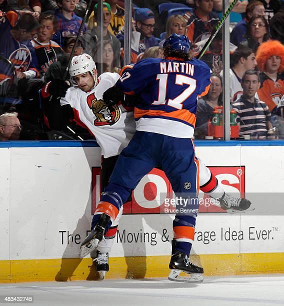 Matt Martin of the New York Islanders hits Clarke MacArthur of the Ottawa Senators into the boards during the second period at the Nassau Veterans...