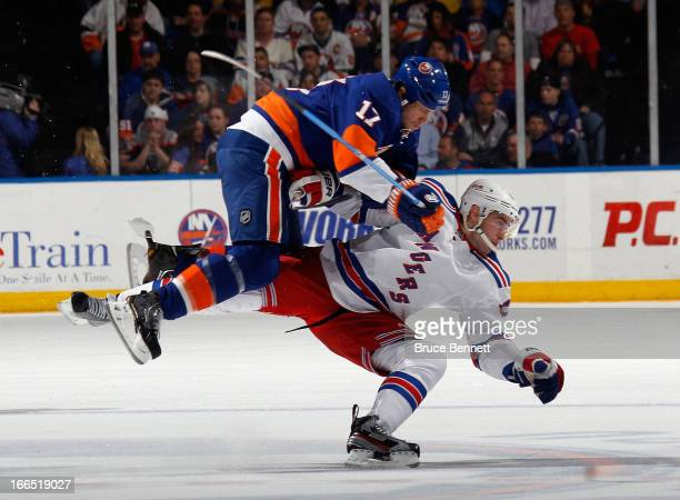 Matt Martin of the New York Islanders hits John Moore of the New York Rangers during the first period at the Nassau Veterans Memorial Coliseum on...