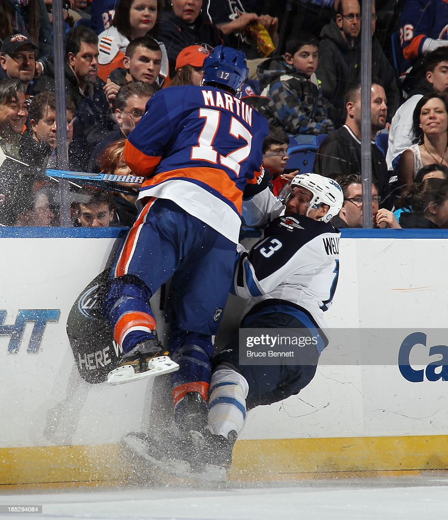 Matt Martin #17 of the New York Islanders hits <a gi-track='captionPersonalityLinkClicked' href=/galleries/search?phrase=Kyle+Wellwood&family=editorial&specificpeople=577984 ng-click='$event.stopPropagation()'>Kyle Wellwood</a> #13 of the Winnipeg Jets during the first period at the Nassau Veterans Memorial Coliseum on April 2, 2013 in Uniondale, New York.