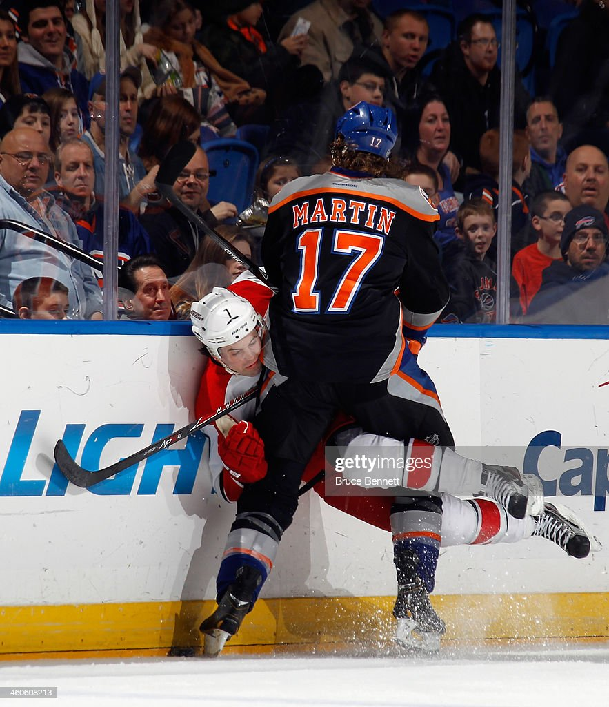 Matt Martin #17 of the New York Islanders hits Ryan Murphy #7 of the Carolina Hurricanes into the boards during the first period at the Nassau Veterans Memorial Coliseum on January 4, 2014 in Uniondale, New York.