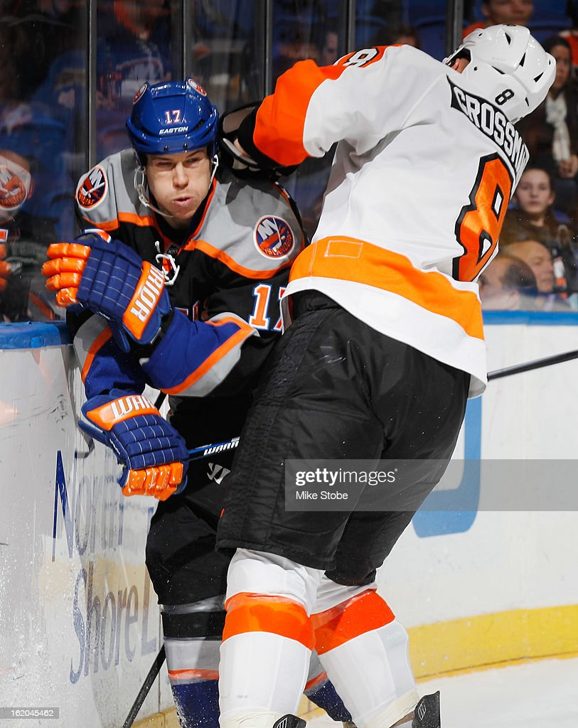 Matt Martin #17 of the New York Islanders is checked by Nicklas Grossmann #8 of the Philadelphia Flyers at Nassau Veterans Memorial Coliseum on February 18, 2013 in Uniondale, New York. The Islanders were shut out by the Flyers 7-0.