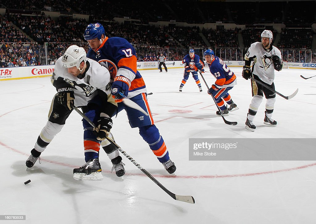Matt Martin #17 of the New York Islanders is held off by Brooks Orpik #44 of the Pittsburgh Penguins at Nassau Veterans Memorial Coliseum on Febuary 5, 2013 in Uniondale, New York.
