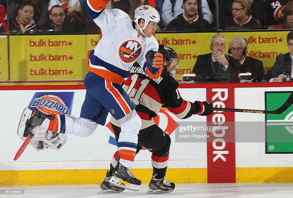 Matt Martin #17 of the New York Islanders jumps to get by <a gi-track='captionPersonalityLinkClicked' href=/galleries/search?phrase=Daniel+Alfredsson&family=editorial&specificpeople=201853 ng-click='$event.stopPropagation()'>Daniel Alfredsson</a> #11 of the Ottawa Senators on February 19, 2013 at Scotiabank Place in Ottawa, Ontario, Canada.