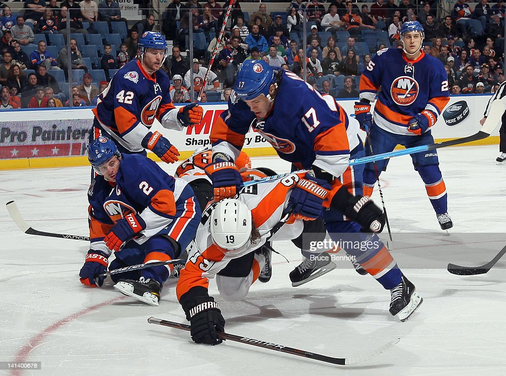 Matt Martin #17 of the New York Islanders knocks down <a gi-track='captionPersonalityLinkClicked' href=/galleries/search?phrase=Scott+Hartnell&family=editorial&specificpeople=201889 ng-click='$event.stopPropagation()'>Scott Hartnell</a> #19 of the Philadelphia Flyers at the Nassau Veterans Memorial Coliseum on March 15, 2012 in Uniondale, New York. The Flyers defeated the Islanders 3-2.