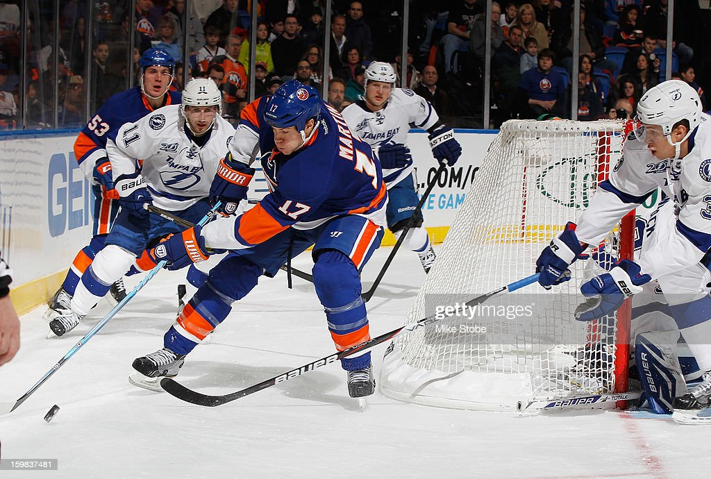 Matt Martin #17 of the New York Islanders lunges for the puck as Keith Aulie #3 of the Tampa Bay Lightning defends the goal at Nassau Veterans Memorial Coliseum on January 21, 2013 in Uniondale, New York.