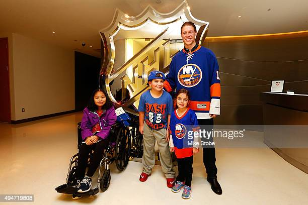 Matt Martin of the New York Islanders Melissa Beach Hockey Fights Cancer kids Dylan Beach and Leanna Pastolero pose for a photo prior to a QA session...