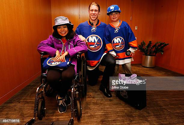 Matt Martin of the New York Islanders poses for a photo with Hockey Fights Cancer kids Dylan Beach and Leanna Pastolero prior to a QA session to...