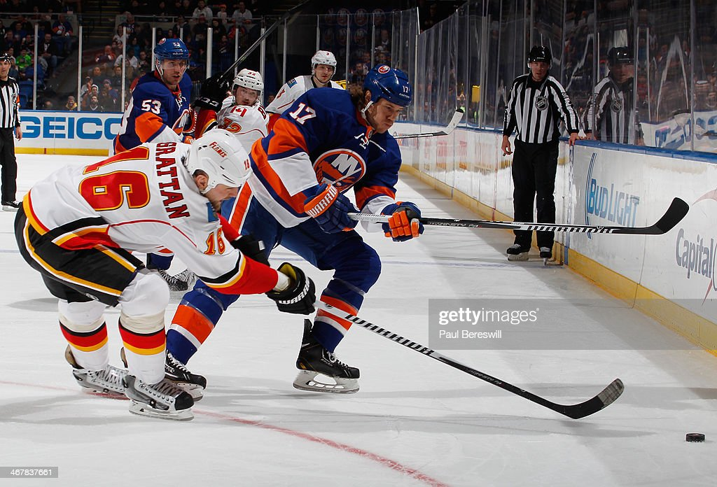 Matt Martin #17 of the New York Islanders skates against <a gi-track='captionPersonalityLinkClicked' href=/galleries/search?phrase=Brian+McGrattan&family=editorial&specificpeople=598177 ng-click='$event.stopPropagation()'>Brian McGrattan</a> #16 of the Calgary Flames during an NHL hockey game at Nassau Veterans Memorial Coliseum on February 6, 2014 in Uniondale, New York.