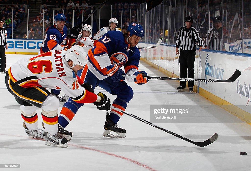 Matt Martin of the New York Islanders skates against Brian McGrattan of the Calgary Flames during an NHL hockey game at Nassau Veterans Memorial...