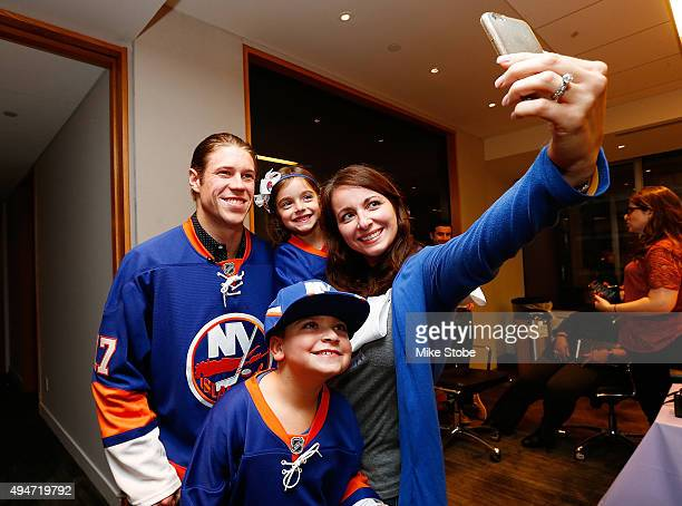 Matt Martin of the New York Islanders takes a selfie with Hockey Fights Cancer kid Dylan Beach his sister Melissa Beach and his mom Amy Beach prior...