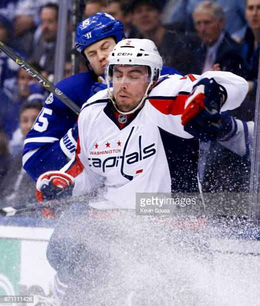 Matt Martin of the Toronto Maple Leafs checks Matt Niskanen of the Washington Capitals into the glass during the second period in Game Four of the...