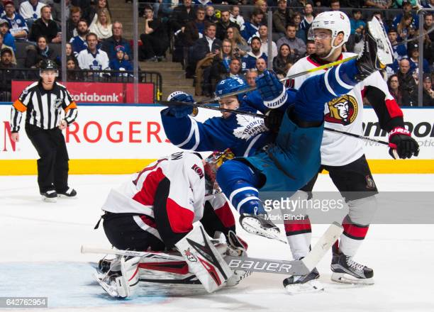 Matt Martin of the Toronto Maple Leafs is upended by Chris Wideman of the Ottawa Senators in front of Senators goalie Craig Anderson during the third...